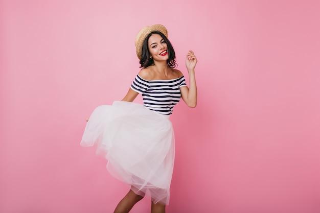 Senhora morena bem torneada com chapéu dançando com prazer. modelo feminino em êxtase com saia exuberante e camiseta listrada se divertindo.