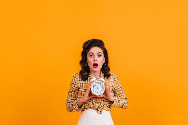 Senhora morena chocada, posando com relógio em fundo amarelo. foto de estúdio de espantada garota pin-up usa camisa quadriculada.