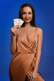 Senhora morena com vestido de seda dourado, ela está sorrindo, mostrando duas cartas de jogar posando na parede azul