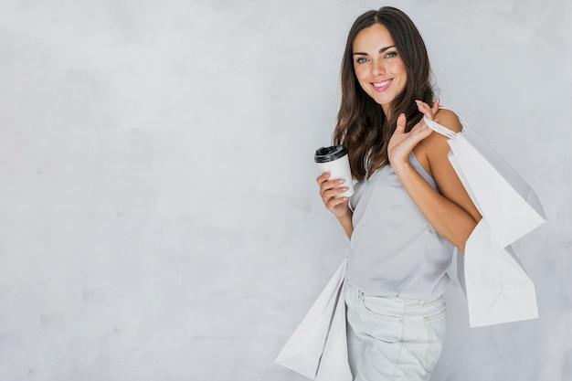 Senhora morena de camiseta com redes de compras e café