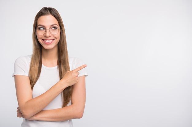 Senhora morena de óculos posando contra a parede branca