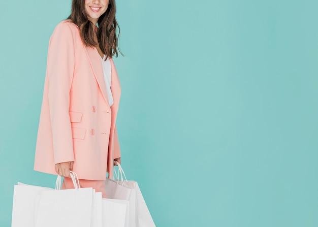 Senhora morena de terno rosa com redes de compras