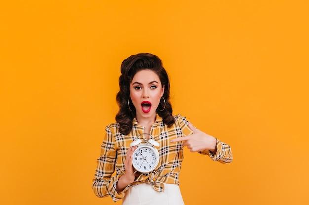 Senhora morena elegante mostrando um grande relógio. foto de estúdio de menina em traje amarelo vintage.