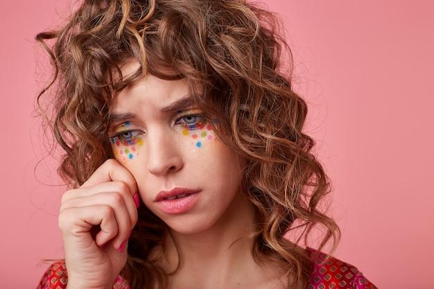 Senhora morena encaracolada chateada com maquiagem festiva posando, enxugando as lágrimas e olhando para baixo com tristeza, estando de mau humor