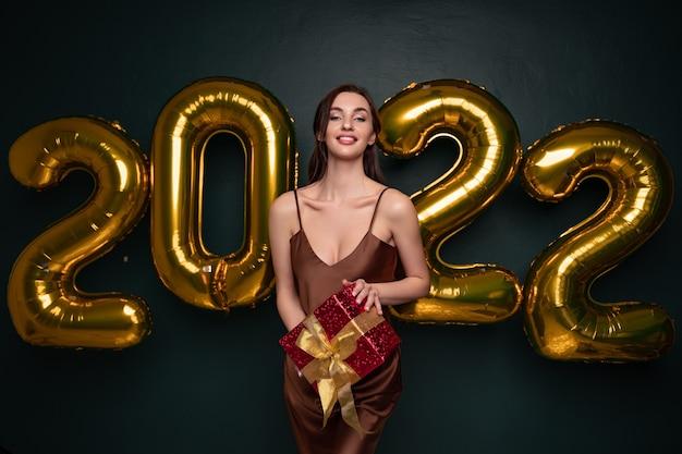 Senhora morena georgeous em lindo vestido segurando a caixa de presente no fundo preto do estúdio com dourado.