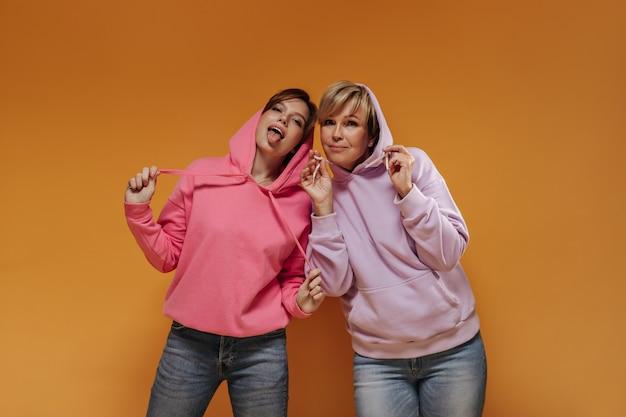 Senhora morena mostrando a língua em roupas rosa e posando com uma mulher loira com moletons lilás em fundo laranja isolado.