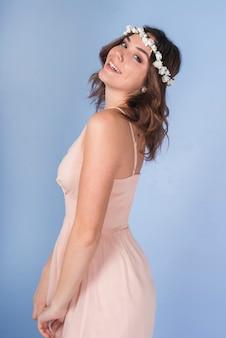 Senhora morena positiva nova no vestido cor-de-rosa com a grinalda da flor bonita