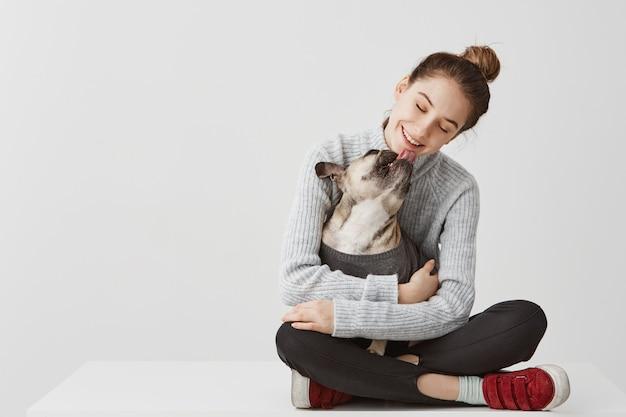 Senhora morena satisfeita em roupas casuais, sentado na mesa, segurando o cachorro nas mãos. designer de inicialização feminino abraçando o cão de raça enquanto lambe o queixo. conceito de alegria, cópia espaço