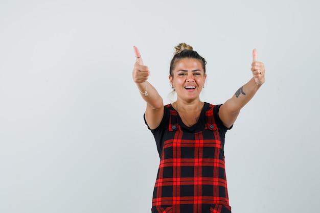 Senhora mostrando dois polegares para cima em um vestido avental e parecendo feliz, vista frontal.