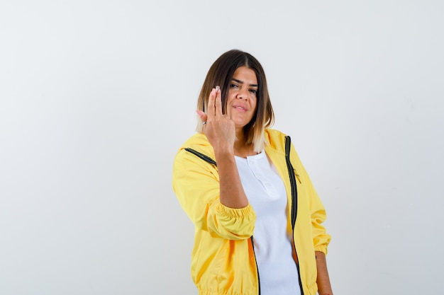 Senhora mostrando gesto de arma em t-shirt, jaqueta e parecendo orgulhosa. vista frontal.
