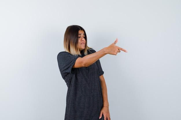 Senhora mostrando gesto de arma em t-shirt preta e olhando com foco, vista frontal.