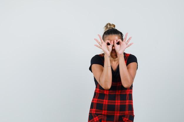 Senhora mostrando gesto de óculos em vestido de avental e olhando focada. vista frontal.