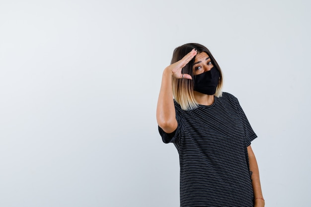 Senhora mostrando gesto de saudação em vestido preto, máscara médica e orgulhoso, vista frontal.
