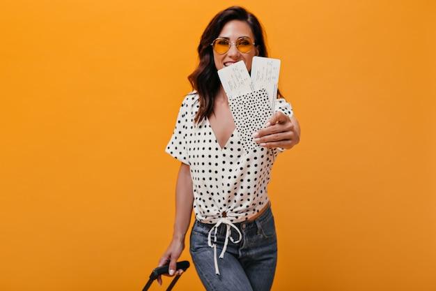 Senhora mostrando passagens de avião em fundo laranja