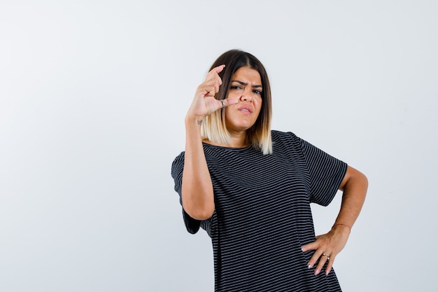 Senhora mostrando sinal de tamanho pequeno em camiseta preta e parecendo insatisfeita, vista frontal.