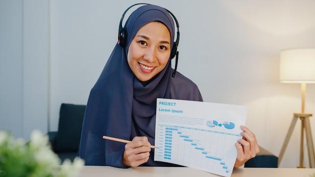 Senhora muçulmana usar fone de ouvido usando laptop para falar com colegas sobre o relatório de venda em videoconferência enquanto trabalha em casa à noite.