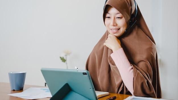 Senhora muçulmana usar fone de ouvido usando tablet digital para falar com colegas sobre o relatório de venda em videoconferência enquanto trabalha em casa na cozinha.