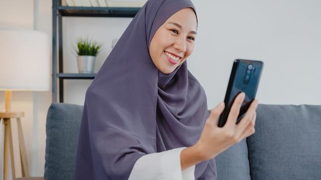Senhora muçulmana usar hijab usando videochamada de telefone falando com o casal em casa.