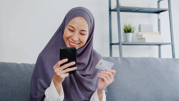 Senhora muçulmana usar telefone inteligente, comprar com cartão de crédito e comprar internet de comércio eletrônico na sala de estar em casa.