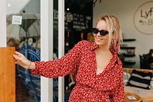 Senhora muito charmosa com vestido brilhante de verão e óculos escuros saindo de uma cafeteria estilosa