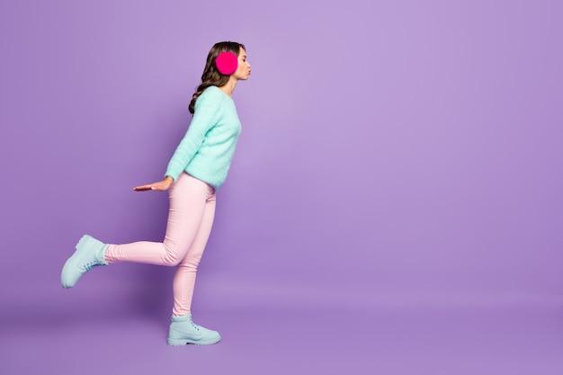 Senhora muito encaracolada enviar beijo ar beijo espaço vazio experiência de encontro às cegas usar pulôver difuso rosa pastel quente orelha cobre botas calças.