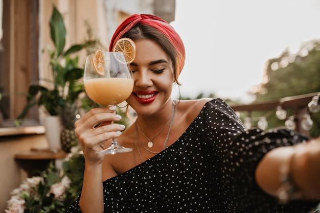 Senhora muito moderna com acessórios de prata, sorriso fofo e bandana brilhante em roupas de bolinhas pretas segurando um copo de coquetel.