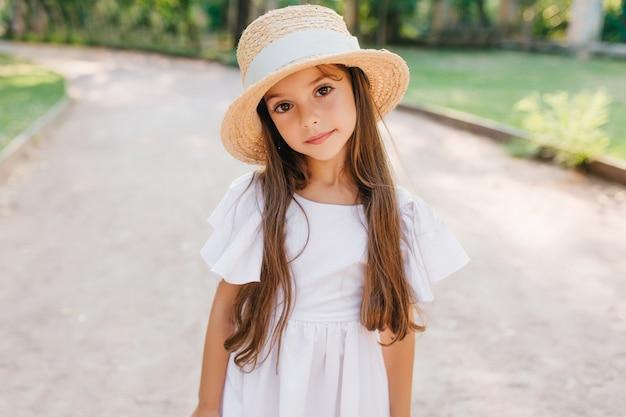 Senhora na moda com cílios longos, olhando com interesse em pé na estrada com chapéu elegante. retrato ao ar livre da tímida garota de cabelos castanhos usando um lindo vestido branco.