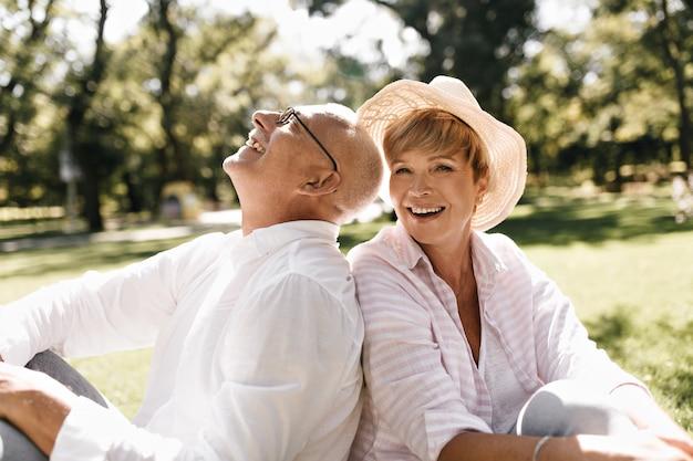 Senhora na moda de cabelos curtos com chapéu leve e blusa listrada, sorrindo e sentado na grama com o velho de óculos e camisa branca ao ar livre.