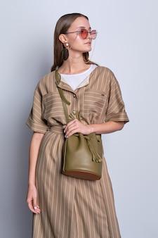 Senhora na moda em grandes óculos de sol, vestido listrado verde-oliva com bolsa de couro posando sobre cinza