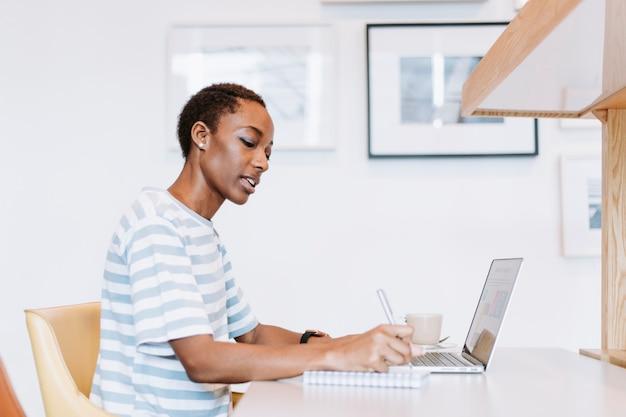 Senhora negra tomando uma nota em uma reunião
