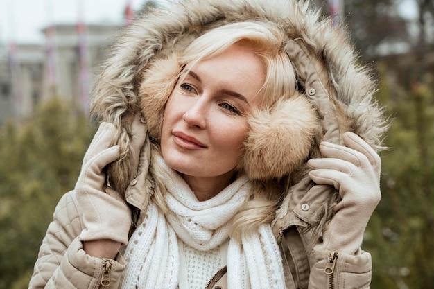 Senhora no inverno usando protetores auriculares e jaqueta com capuz