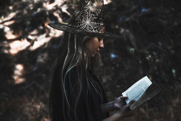 Senhora no livro de leitura de fantasia de bruxa