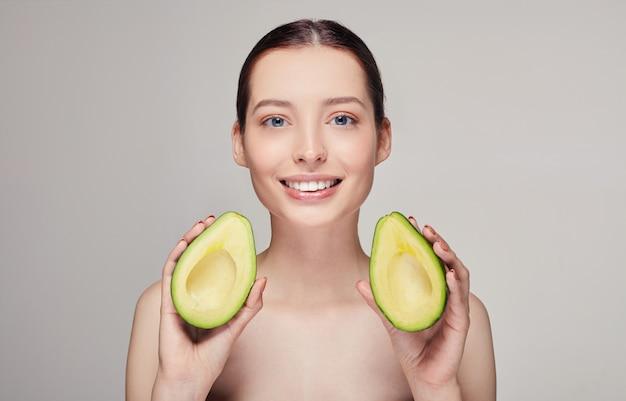 Senhora nua com sorriso perfeito e abacate nas mãos