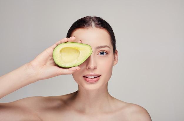 Senhora nua concurso atraente com abacate na mão direita perto do olho