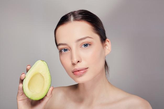Senhora nua pensativa com pele de brilho puro perfeito com abacate na mão
