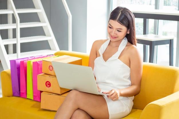 Senhora ocasional asiática nova que trabalha o empreendedor pequeno negócio startup pme na loja de roupa.