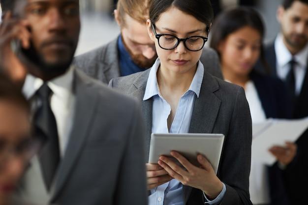 Senhora ocupada lendo o documento no tablet em pé na fila