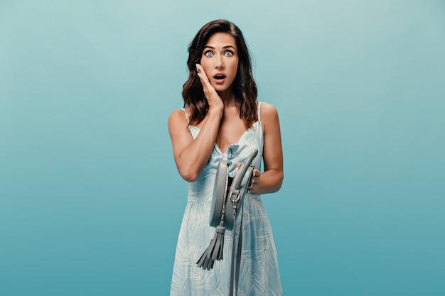 Senhora olha para a câmera com espanto e posa com a bolsa aberta sobre fundo azul. garota surpresa com olhos grandes em poses de vestido de verão luz.
