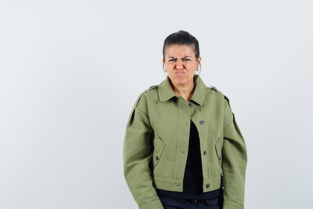 Senhora olhando para a câmera enquanto carranca com jaqueta