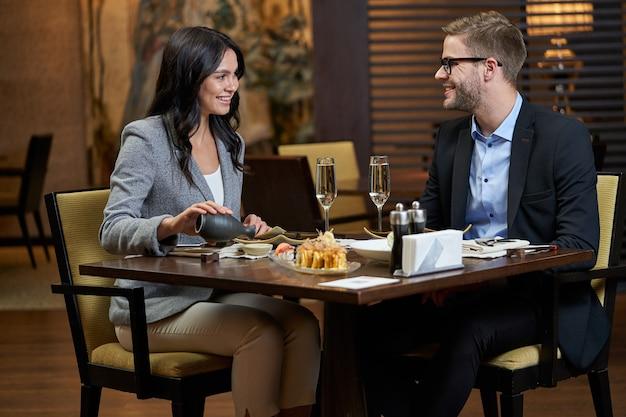 Senhora olhando para um homem enquanto conversa à mesa e coloca o molho de uma garrafa preta em um copinho
