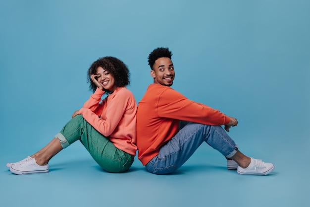 Senhora otimista e seu namorado sorriem e posam sentados na parede azul