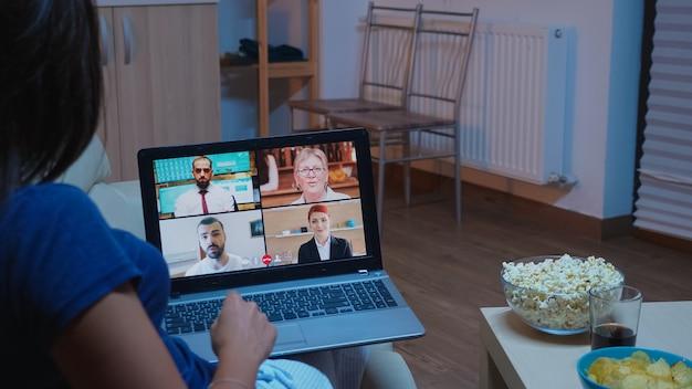 Senhora participando de um webinar sentada no sofá. trabalhador remoto em reunião on-line, consultoria de videoconferência com colegas em videochamada e bate-papo por webcam trabalhando na frente do laptop