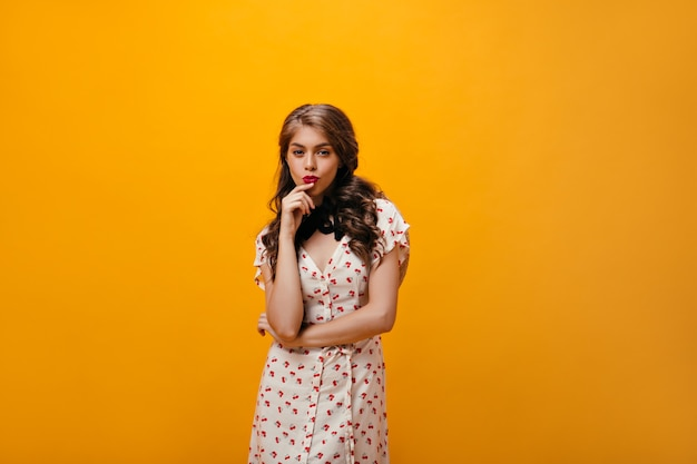 Senhora pensativa em poses de vestido branco em fundo laranja. mulher atraente com penteado ondulado em roupas da moda, olhando para a câmera.