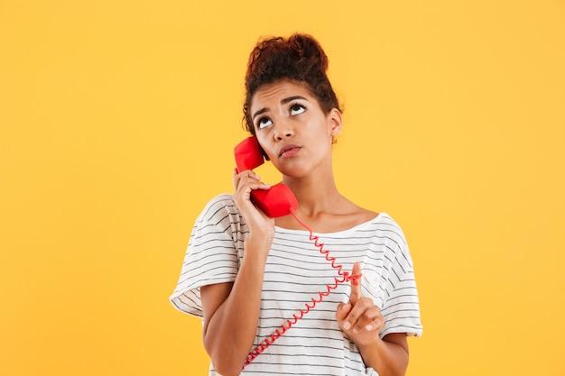 Senhora pensativa pensativa, falando no telefone vermelho isolado