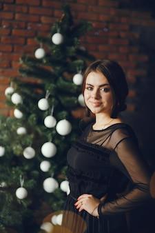 Senhora perto de uma árvore de natal.