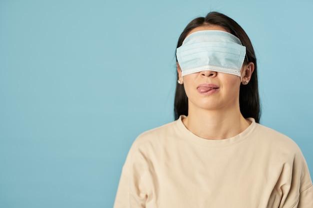Senhora posando em estúdio com máscara antivírus