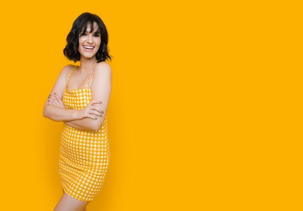 Senhora posando feliz em um vestido amarelo