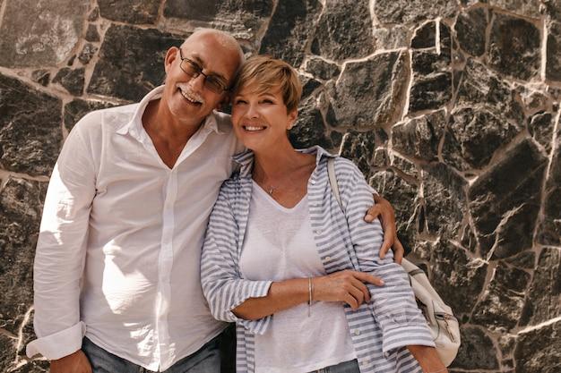 Senhora positiva com cabelo curto loiro em blusa azul e camiseta branca sorrindo e se abraçando com um homem de óculos e camisa leve