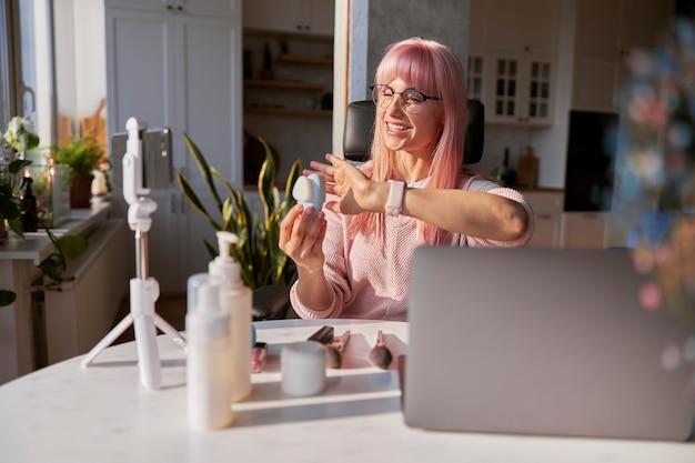 Senhora positiva com óculos apresenta um vídeo em casa com a escova elétrica de limpeza facial