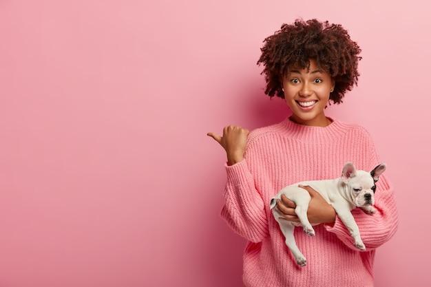 Senhora positiva de pele escura aponta o polegar para longe, usa um macacão casual, segura o cachorro dormindo